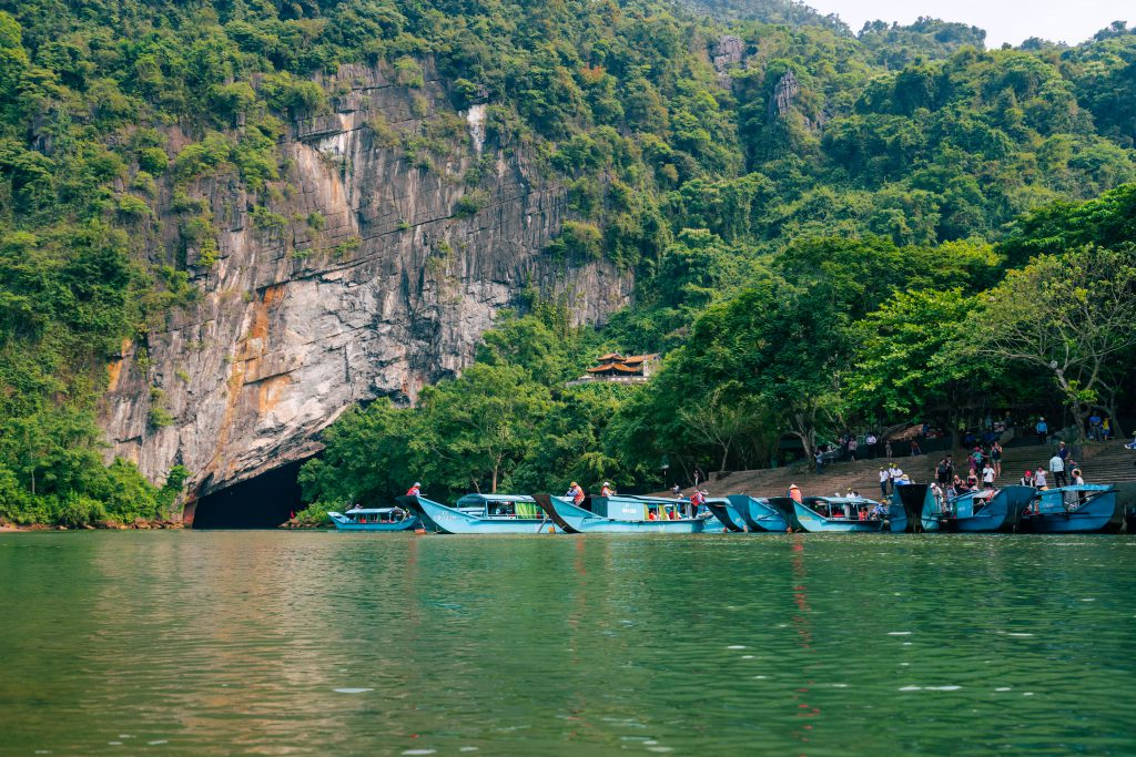 phong nha cave with many blue boat waiting for guests in front of its entrance