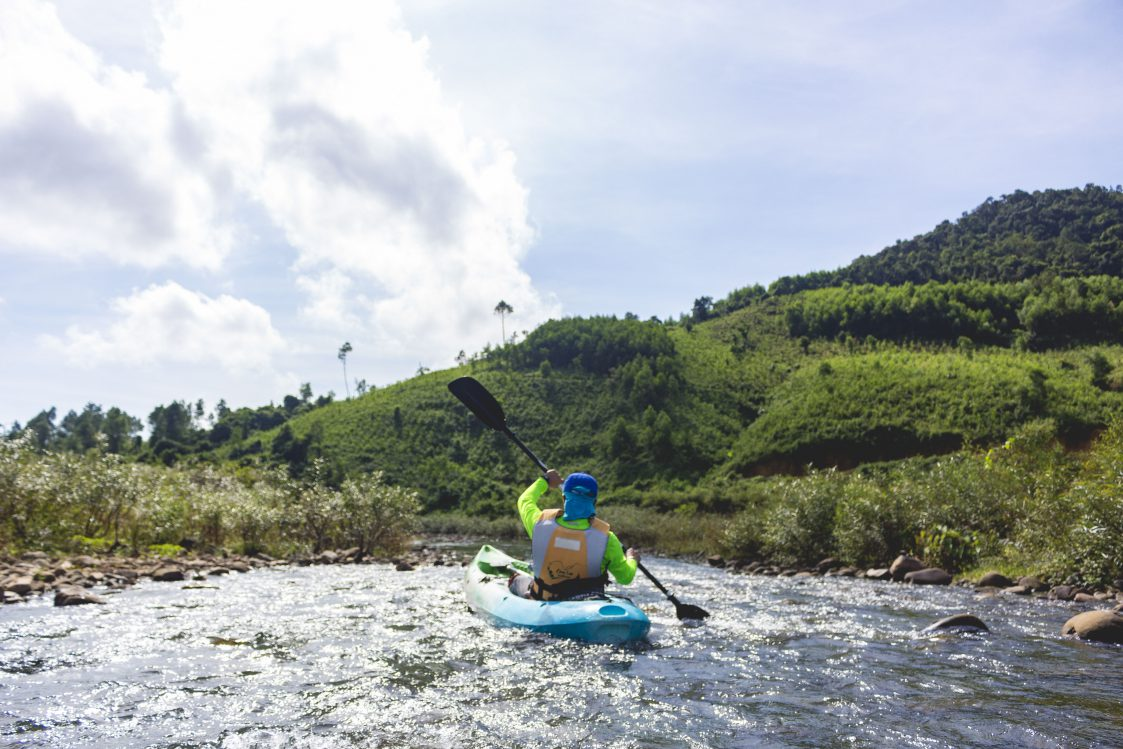 backside of a man kayaking on river in phong nha