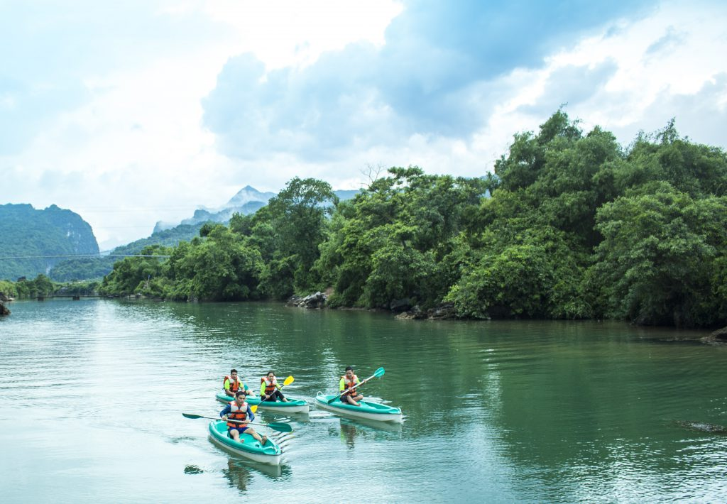 group of friends kayaking on river in phong nha