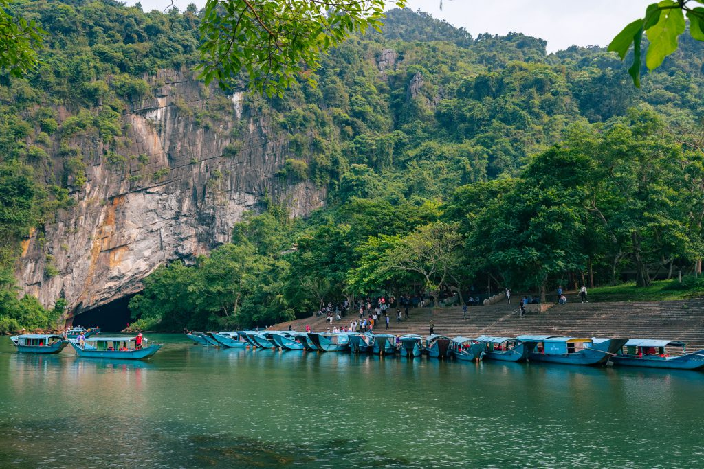 blue boats waiting for guests in front of phong nha cave's entrance