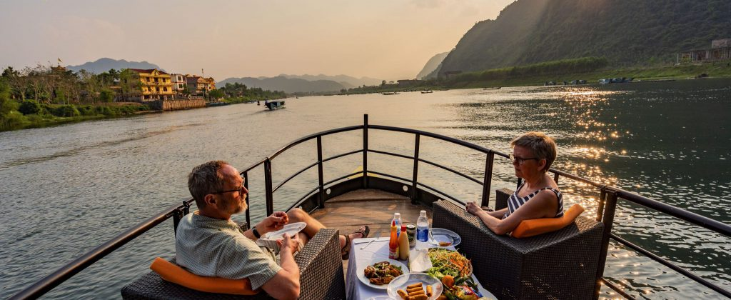 couple enjoy food at the bow of a boat watching the sunset in phong nha