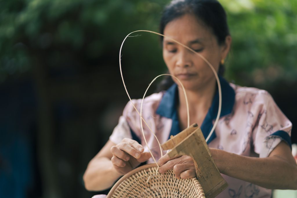 a woman weaving a rattan basket