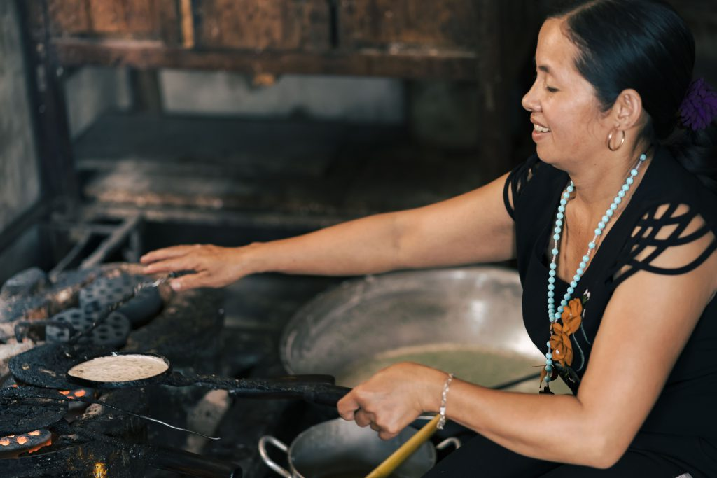 a woman cooking over open fire stove