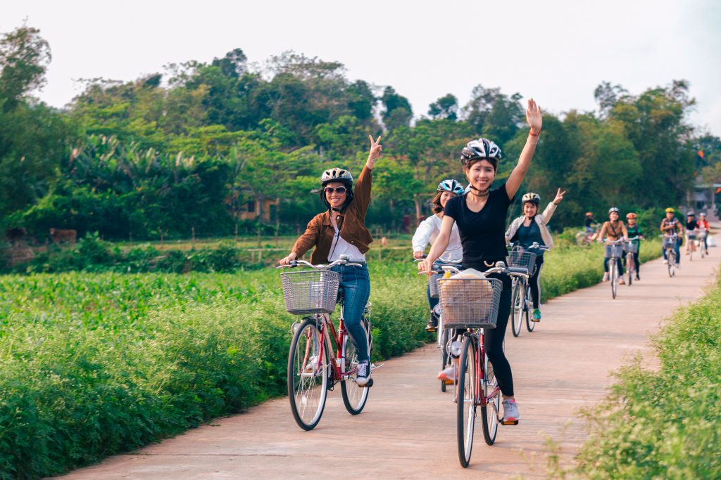 people are waving and looking happy while biking along village road and passing by corn fields